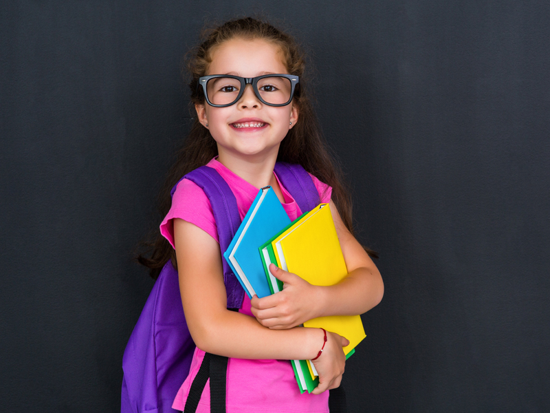 A little girl wearing glasses holding school supplies