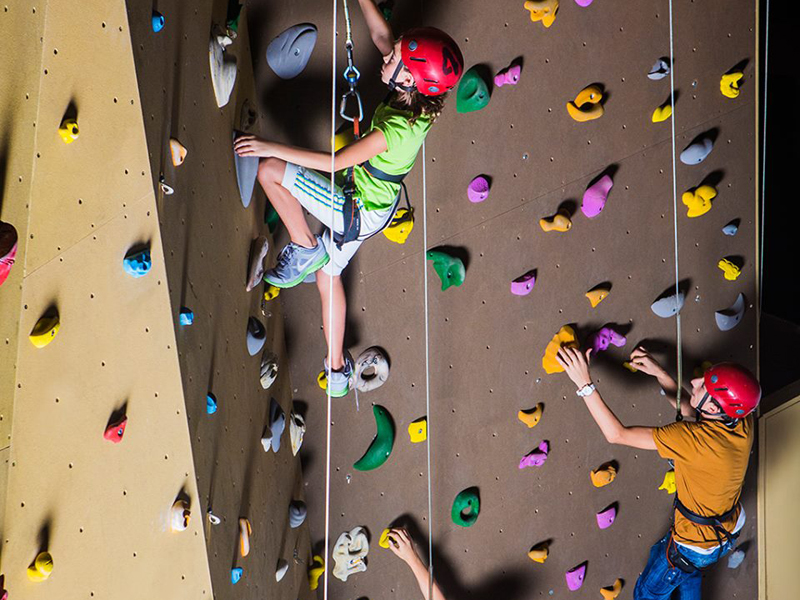 A family on an indoor rock climbing wall at Sky Trail in City Centre Mirdif