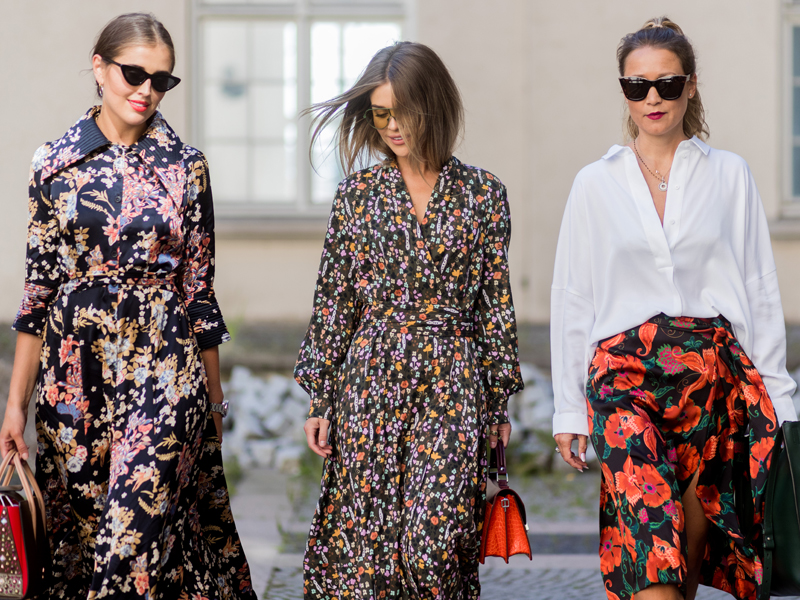 A street style shot of three fashionably dressed young women