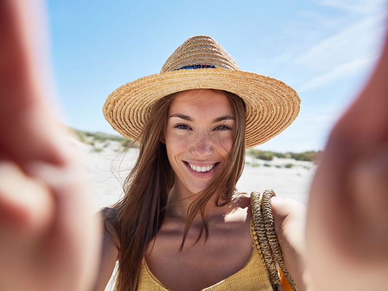 Smiling woman wearing a straw hat on the beach