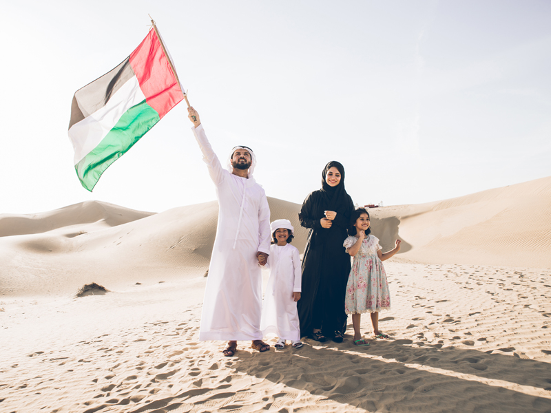 Emirati family in the desert holding a UAE flag
