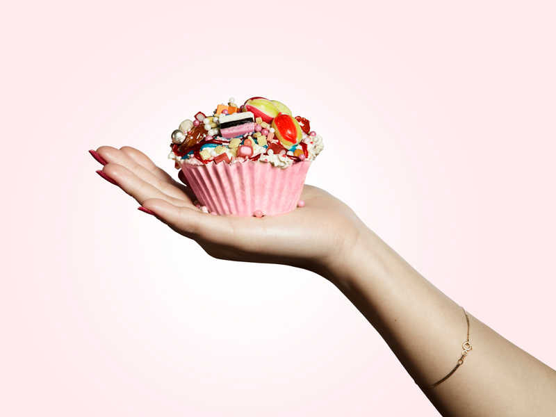 A woman's hand holding a pink cupcake