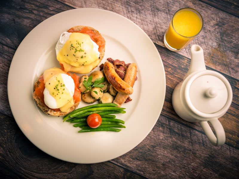 Eggs Benedict Royale from La Brioche on a wooden table with a pot of tea and glass of orange juice