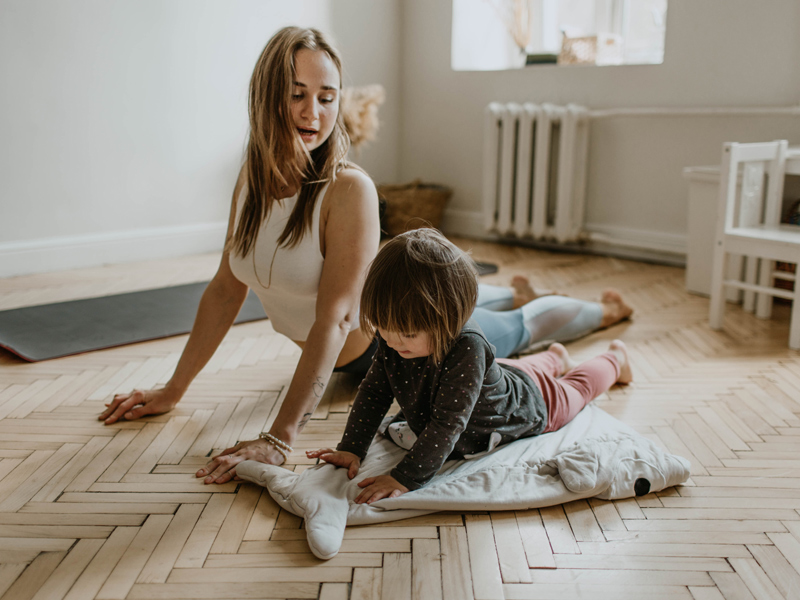 A mother & daughter practicing yoga at home