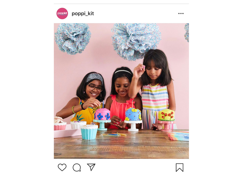 Three young girls decorating colourful cakes
